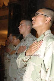 soldiers hold their hands to their hearts while saying the pledge of allegiance